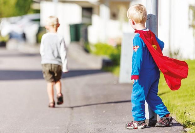 Gutt i Supermann-kostyme som ser etter en annen gutt som går sin vei